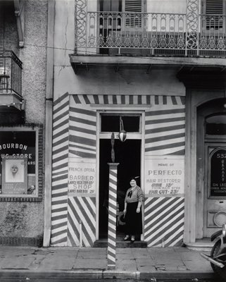 small storefront with woman in dark skirt standing in open doorway; stripes painted on walls around doorway and on pole on sidewalk; balcony on floor above shop