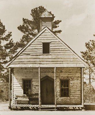 very small, simple, old wooden building with peeling paint; small cupola; door has pointed lintel; small window in gable; bench to L of door