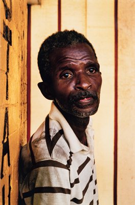 black man wearing brown striped shirt, sitting against wall with black lettering
