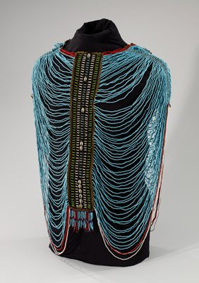 capelette/shoulder covering made of strands of beads--red, blue and white--in loops from center to shoulders, front and back; shoulder pieces (reinforced with metal) with openwork thread and bead designs in black, blue, white and green beads with cowrie shells; hanging bead strands of red, dark blue and light blue beads at shoulders; central ornament on each side with blue and red bead strands, stuffed cotton cloth roll and iron loops