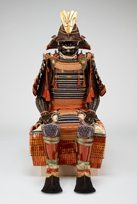 suit includes helmet with praying mantis maedate (forecrest), menpo (face mask), torso covering, pair of front shoulder medallions that attach to torso covering, pair of large upper arm guards, pair of small shoulder coverings (each with a pin for attachment), pair of gauntlets with arm and hand guards, apron, pair of tsutsu suneate (leg guards), and pair of kote (boot coverings); see Components for descriptions of each piece