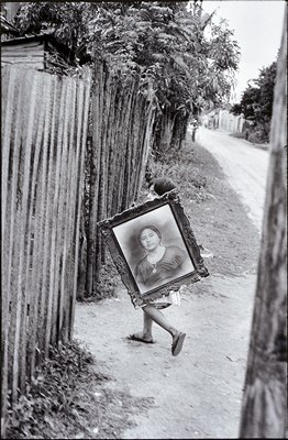 child carrying a framed painting of a woman
