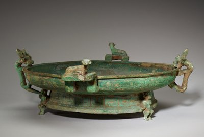 The disposition of this vessel is unusual, for, despite the fact that it has the broad shallow bowl and deep foot of its class, it does not rest on the foot proper. It is supported instead by three small human figures facing outward as they grip the rim of the foot. their bent knees suggest clearly the weight of their burden, as does the strained positon of their heads, held close to the bottom of the bowl and bearing part of its weight. On each of two handles of the bent ear type, an ox reclines calmly, its head turned outward, its legs folded under the body. The division of the vessel into the usual four sections is achieved by two more animals contrasting strongly with the placid oxen. These are dragons that climb vigorously up the sides of the bowl and bite on its rim. The neck belt displays the broad, figured bands of Middle Chou and the foot carries a band of hanging scales of an advanced, almost squared type. Patina sharp green with patches of blue.