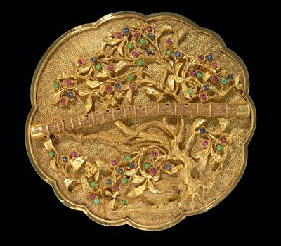 Gold presentation box; round, scalloped border; chased with swastika-fret design. Bears flute, emblem of Han Hsiang Tzu, surrounded by sprays of spun gold leaves and flowers picked out with small cabochon rubies, sapphires and green jade. One of a set of 8 presented to Emperor Ch'ien Lung in the 43rd year of his reign.