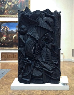 matte black patina; relief carving with pairs of guns and saws, feathers, roundel with open book and flames; rectangular