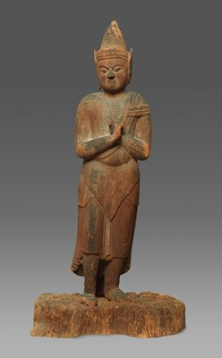 standing figure with a conical hat with ear flaps, long skirt and cloak draped over the left shoulder; figure is standing on rock formation with palms up and crossed at the wrist across the chest; base