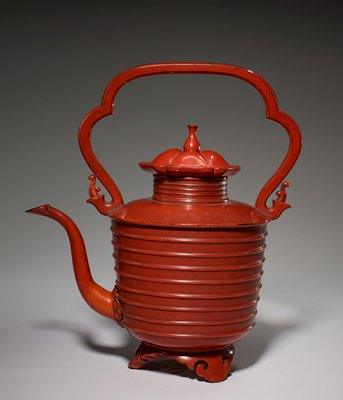 red lacquered kettle with long, delicate spout, scalloped, erect handle, concentric raised rings around body; stands on three carved feet; flower-like lid with long, spindly knob