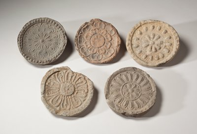 round roof tile end with floral design; beaded piping around outer ring