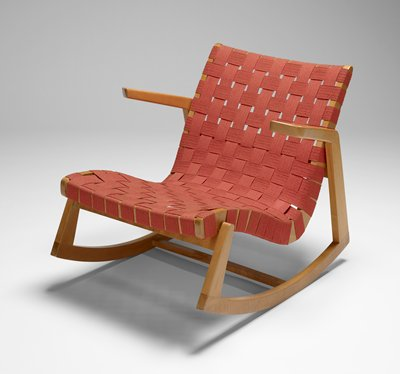 small, low rocking chair; light-stained wood frame; woven dark orange cotton webbing on back and seat; wedge-shaped wood arms