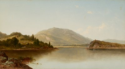 view over calm lake with mountain in background; green landforms with trees at left and right; rocks and grass in LLC; a few clouds in URQ