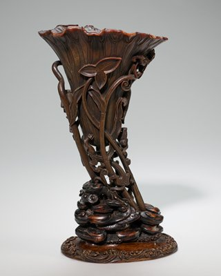 carved rhinoceros horn libation cup; in form of a lotus leaf; the exterior is decorated in designs of lilies and flowers carved in high relief; the interior is carved to show the numerous veins of the leaf; carved wood base