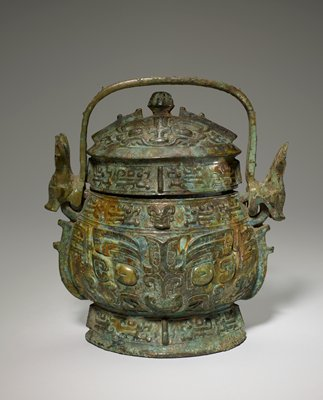 Wine can, so-called 'Yu', inscribed. This vessel, broad and oval in section, has a bow-shaped handle attached to rings at the ends of the oval. These rings, together with free animal's heads on the long side of the oval, serve to divide the neck belt into four panels. On the lid and foot, decor belts are divided into four panels by simple flanges. The body and the cupola of the lid, interrupted only by two unsegmented flanges at the ends of the oval, constitute two large fields for the principle decor, executed in rather high, rounded relief on a bare ground, unusual in this vessel class. Two consecutive winged dragons appear in each panel of the narrow belts, those in one panel antithetically placed to those in the next. The body of the vessel displays a bodied t'ao-t'ieh, its vertically rising body and leg detached from the forcefully modeled head. The t'ao-t'ieh of the lid faces the same way as that on the body. The animal head at the end of the handle is a remarkable feature of this vessel. In general, it resembles the ordinary t'ao-t'ieh, but the horns are highly eccentric. Basically the well-known 'bottle horns', they are flattened at the top into a five-fingered leaf centered by a big eye in the same high, rounded relief as that in the animals' face. Patina green with patches of brown.