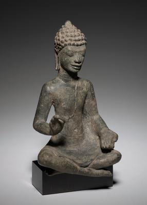 Buddha seated with legs crossed at the ankles. He wears a monk's diaphanous garment which covers only his right side. He is seated in a adamantine pose with the soles of his feet facing upward (as in early Gupta art). He assumes a gesture of exposition with his very long fingers. His face is excellently modelled with heavy eyelids, eyes looking downward and an enigmatic smile. His ears are large with long perforated lobes and he wears a tiered snail-like hairdo. Original and dark patina. Dvaravati style, Mon, Thailand. Cast in the lost wax process.
