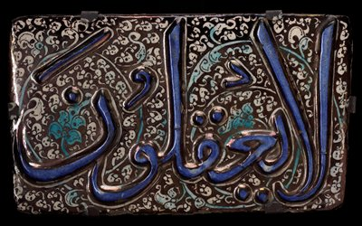 Tile, Sultanabad, pottery, with raised blue inscription on black and white floral background.