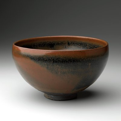deep bowl with low, slightly flaring ring foot; curved sides; blue-black glaze over brown on interior and exterior; brown slip on foot