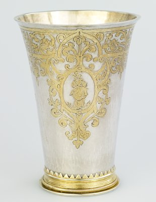 parcel gilt beaker of tapered cylindrical form, engraved with foliate strapwork, enclosing three cartouches of male and female figures, moulded foot with corde band and serrated edge, engraved beneat with armorials, silver gilt