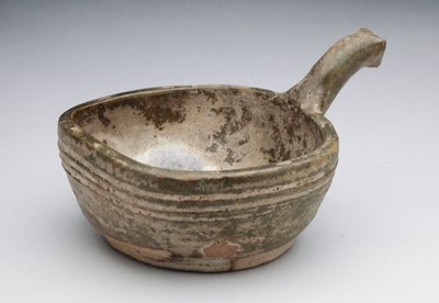 Bowl, ladle-form, circular body pressed at rim to form right angle with short curved handle rising at one side and terminating in a simple animal's head (drinking bowl); reddish-clay, green, irridescent glaze
