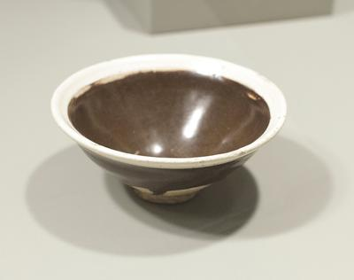 Tea Bowl, Honan ware; flaring sides rising from ring foot; unglazed exterior and brown glazed interior with band of cream-white at top; pottery