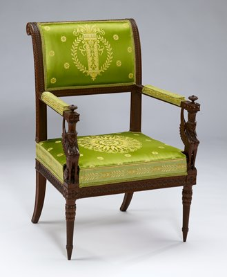 armrests supports formed by carved figures of sphinxes; topped by fluted knobs; the back scrolling into rosetted ears and carved with acanthus leaf pattern; the seat rails carved with a rosette motif; on fluted spiral legs terminating in collars of plantain leaves