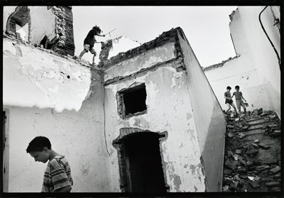 children playing in the ruins of a building; one child near top of image; two on right descending stairs; one in the foreground looking down