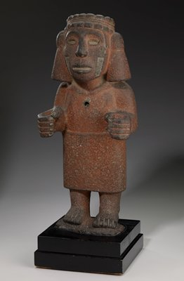 stone figure with red pigment stands on black wood base with hands touching index figure to thumb; face incised on either side with rectangular markings; headdress crowns figure with large ear ornaments; small drill hole in center of chest