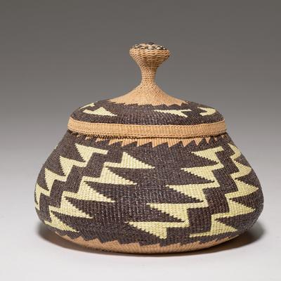 round basket with stepped, geometric pattern; light yellow stepped diagonal zigzags throughout black/dark brown body; light brown rim; corresponding pattern on circular cover with knob; light brown interior with four black and yellow A-shapes around sloped center base