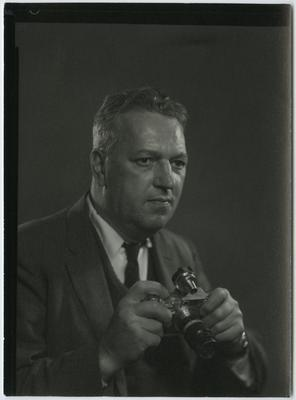 Black and white photograph of a man wearing a suit holding a camera and looking to the viewer's right; image cropped below his hands