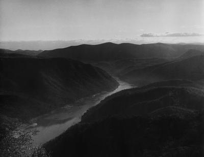 Black and white photograph of a landscape with a river in a vallery between low mountains