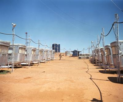 Color photograph of rows of silver camper-type dwellings on a flat sandy lot; clear blue sky