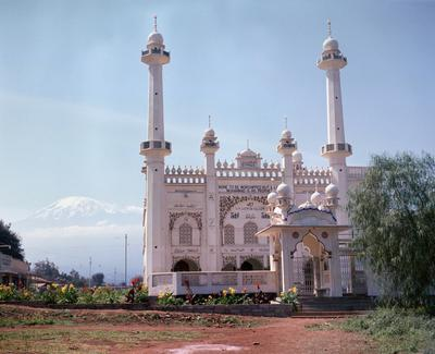 Color image of the facade of a mosque with flowers out front; a mountain can be seen in the background along the left side