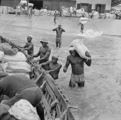 Black and white photo of figures wading into water and holding onto a boat; one figure with a white sack over his shoulder