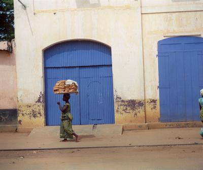Color image of a woman carrying a platter of bread on her head while she walks in front of a set of blue doors