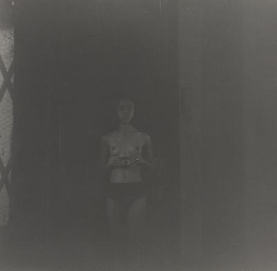 dark black and white image of a woman wearing black briefs holding a camera in front of her belly; small strip panel of chicken wire glass at left with diamond-shaped lattice on top of it; received in silver frame