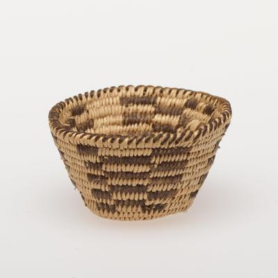 Miniature round basket with flared sides; coiled. Design consists of four checkered panels. Colors are natural and black.