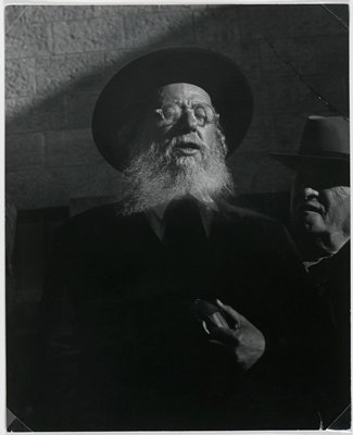 black and white photograph of bearded man wearing glasses and hat with man in hat standing on right