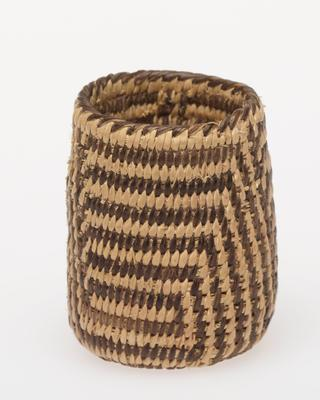 Miniature vertical-walled, deep basket; coiled. Design consists of horizontal bands broken by diagonal bands that form triangles. Colors are natural and black.
