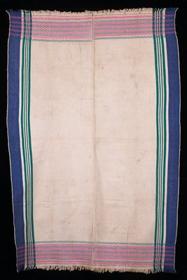 predominately tan blanket; one wide blue and four narrower green stripes on lengthwise edges; pink and green geometric designs in stripes along edges of width; fringes; lengthwise center seam