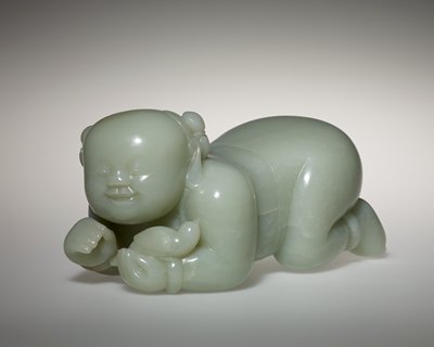 the nude boy shown crouching in an almost horizontal position, holding a bird in his left hand, the chubby face with simply carved features and the hair pulled back in double knots; carved from greenish white stone. Former Classification: Jade
