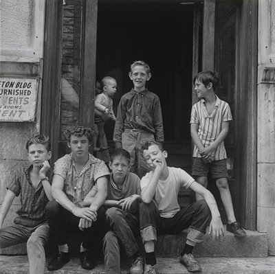 four boys seated on a step in front of an apartment building; two boys standing in front of open door; baby and two other figures visible inside door at left