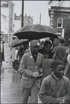 line of people on a city sidewalk; two boys in foreground in front of a large woman under an umbrella, wearing a rain bonnet and carrying a cardboard sign