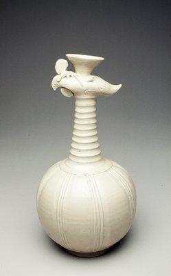 for Indonesian export market; white glaze; globular body surmounted by ringed neck tapering toward a flattened stylized phoenix head with applied details, below a trumpet-form mouth