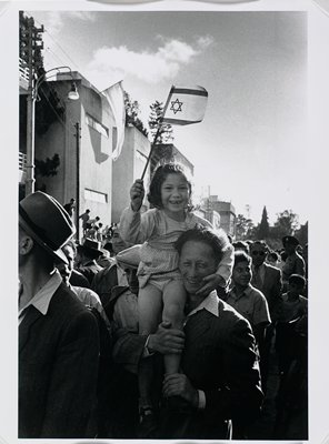 black and white photograph of girl holding Israeli flag seated on the shoulder of a man in a crowd
