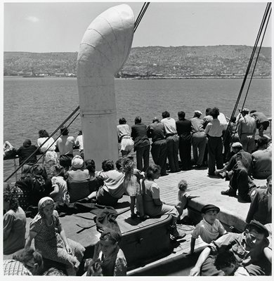 black and white photograph of people seated and looking over railing of the deck of a ship