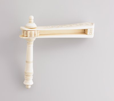 ivory noisemaker; extension carved with flowers and crosshatched designs; plexi stand