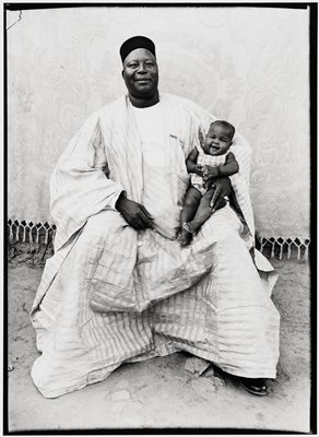 Dressed in a loose boubou, a white smock (forokoni), and a black fez, this wonderful giant known to everyone in Bamako is proud of his lovely daughter.