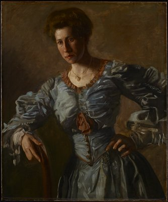 Portrait. Three-quarter figure facing spectator, right hand on back of chair; left on hip. Hair worn in pompadour style of early twentieth century. Greyish-blue taffeta dress trimmed with ruching of cocoa brown silk.