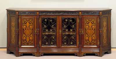 sideboard with beveled front corners; double glass doors at center with metal foliate grills in front of glass; inlaid foliate decorations on doors flanking glass doors and on sides; carved foliage at top under edge and on molding