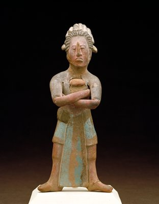 Whistle in the form of a Dignitary; Island of Jaina style. Figure stands with arms crossed and feet spread well apart. The costume consists of a short, two-tiered skirt with a wide panel descending to feet in center front. Stylized hair with feathered headdress, pectoral, earrings. The face is well modelled, with arched nose and flattened brow. A whistle, modelled in left shoulder blade, makes clear musical note when blown. Painted in blue, red, black,and white. An unusually fine example.