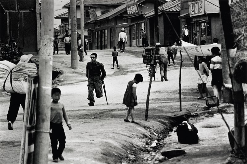 street scene with children in foreground; man on crutches missing lower leg in center; buildings on both sides of street