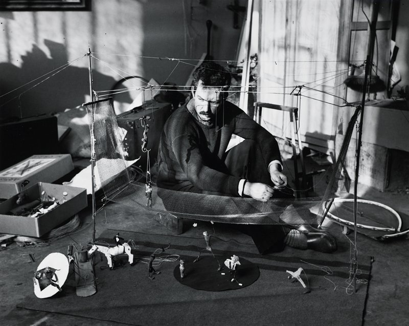 Calder seated on floor, wearing a sweater, slacks and clogs, working with strings attached to a model circus trapeze; horse, tumblers and other small figures below trapeze net